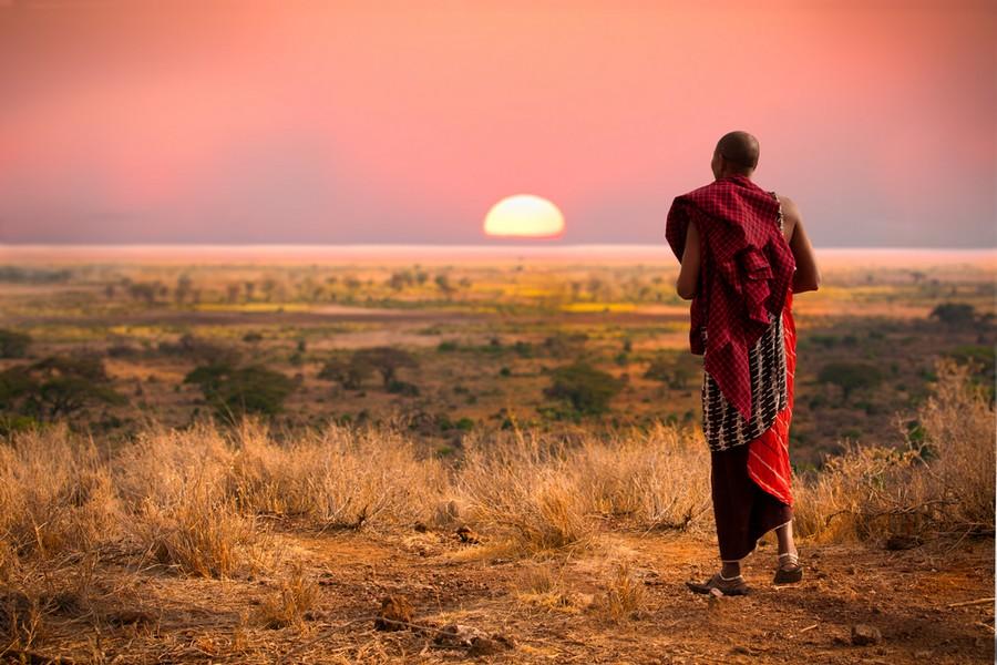 Un Masai osserva il tramonto sulla pianura del Serengeti nell'area della Tanzania